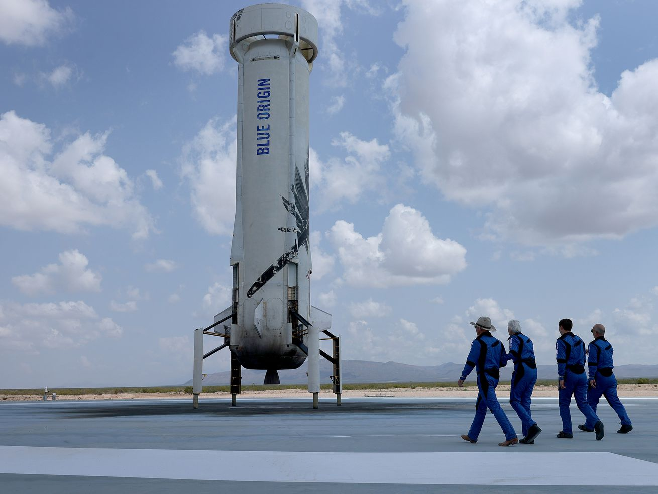 Blue Origin's New Shepard crew Jeff Bezos, Wally Funk, Oliver Daemen, and Mark Bezos walk near the booster rocket to pose for a picture after their flight into space.