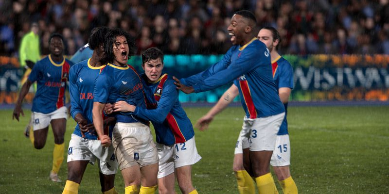 The players from AFC Richmond gather around Dani Rojas to celebrate his big goal.