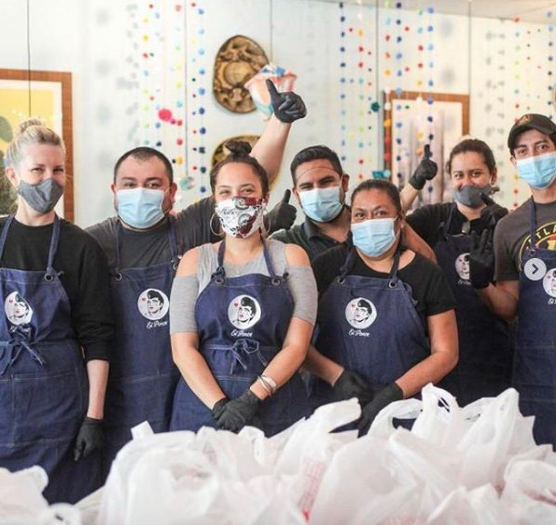 A group of restaurant workers wearing aprons and face masks, standing in front of a pile of plastic bags.