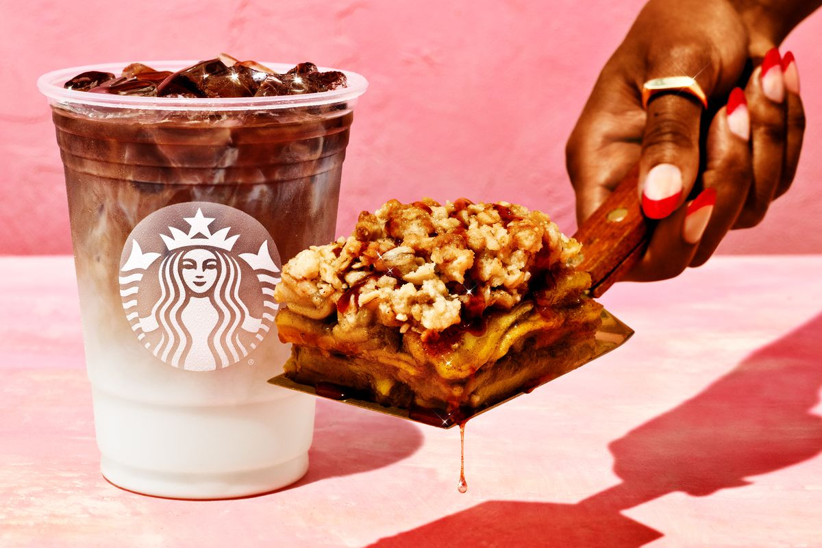 A plastic cup with a white and brown layered starbucks drink in the background. In the foreground, a manicured hand holding a spatula with a slice of crisp