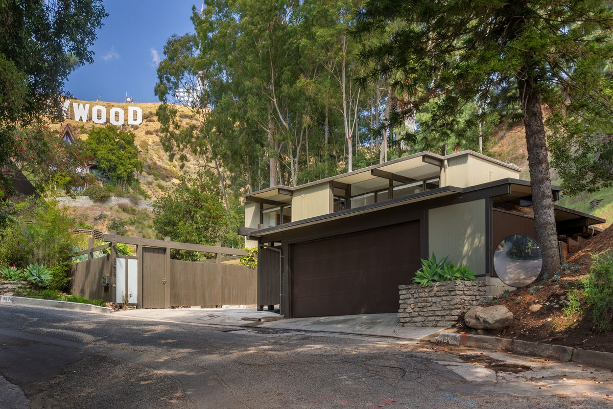"""A garage and house at the base of a hill, with large white letters in the background spelling out """"WOOD"""""""