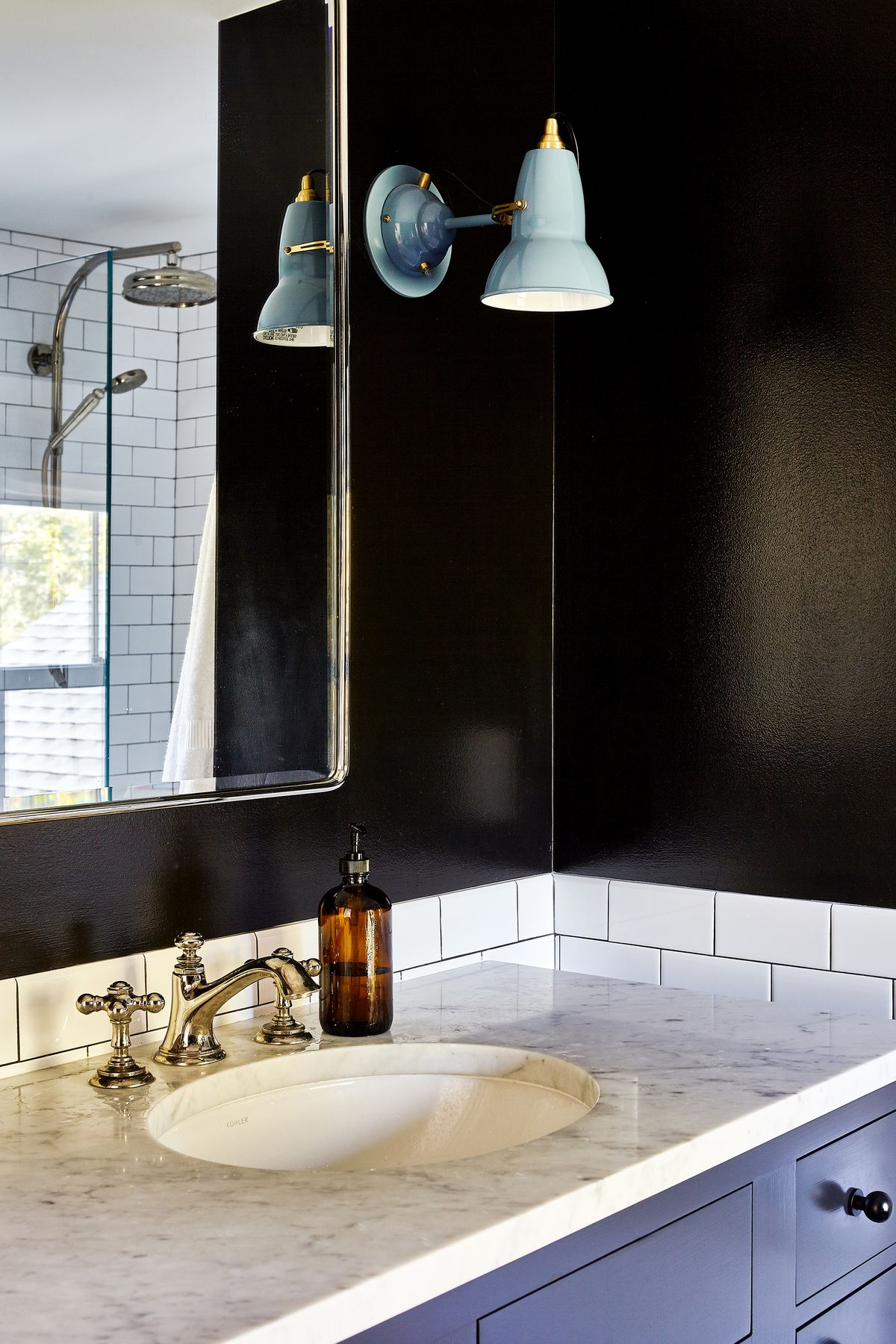 A bathroom has black walls and white tile, with powder blue sconce lights.