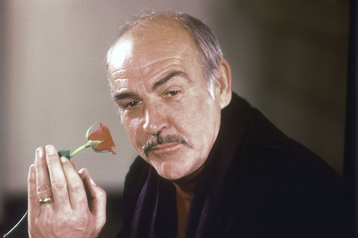 """Actor Sean Connery holds a rose in his hand as he talks about his new movie """"The Name of the Rose"""" at a news conference in London in 1987."""