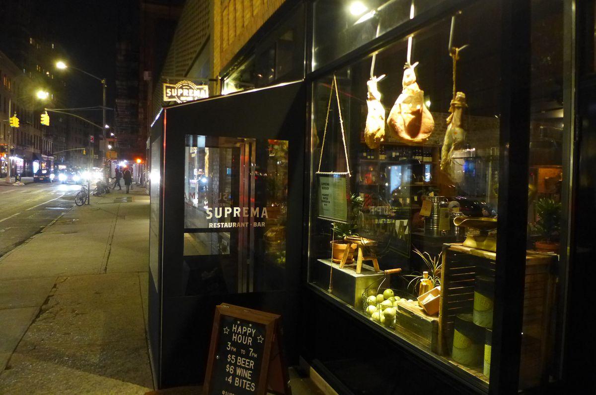 A darkened restaurant facade on a darkened street.