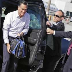 U.S. Secret Service agents hold open the door as Republican presidential candidate and former Massachusetts Gov. Mitt Romney gets out of his vehicle before he boards his campaign plane in San Francisco, Saturday, Sept. 22, 2012.