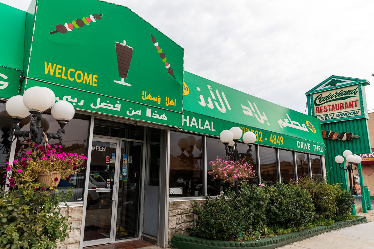 The green awning and flowers with a kabobs and a vertical meat spit illustration on the front of Cedarland Restaurant.