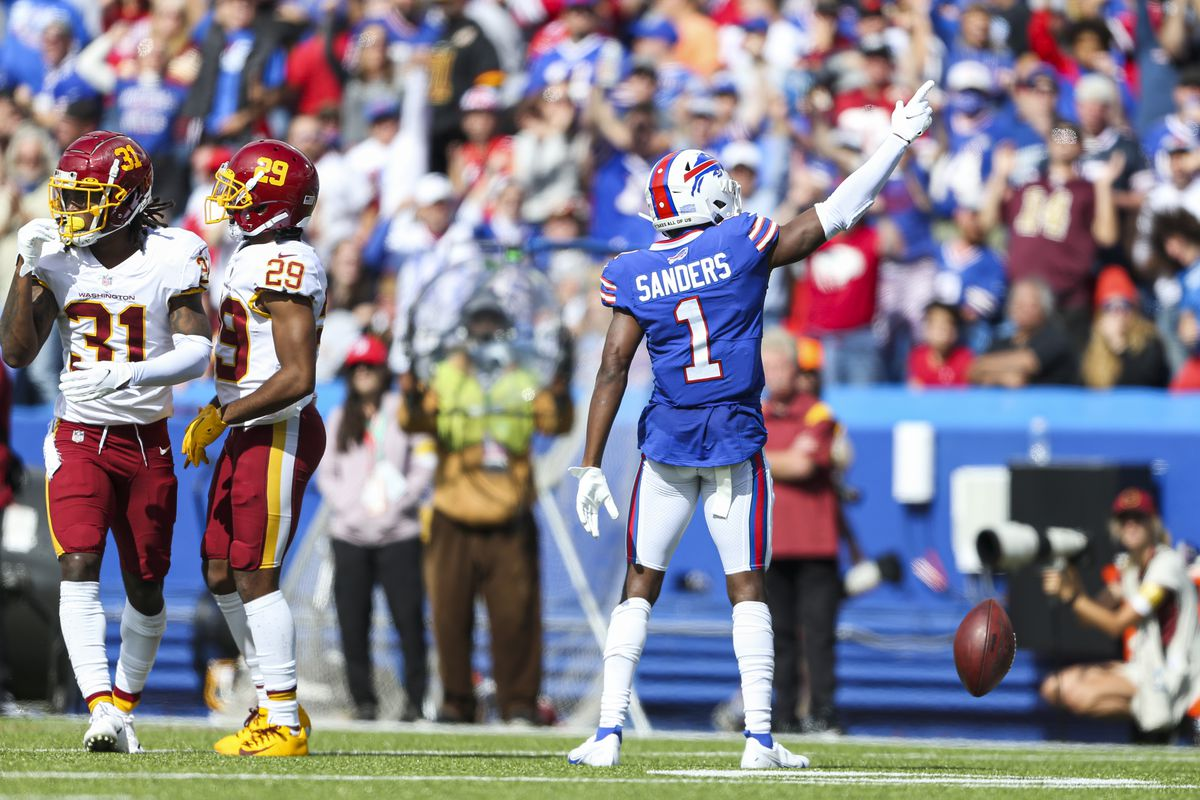 Emmanuel Sanders #1 of the Buffalo Bills celebrates after making a catch while defended by Kendall Fuller #29 and Kamren Curl #31 of the Washington Football Team during the second quarter of the game at Highmark Stadium on September 26, 2021 in Orchard Park, New York.