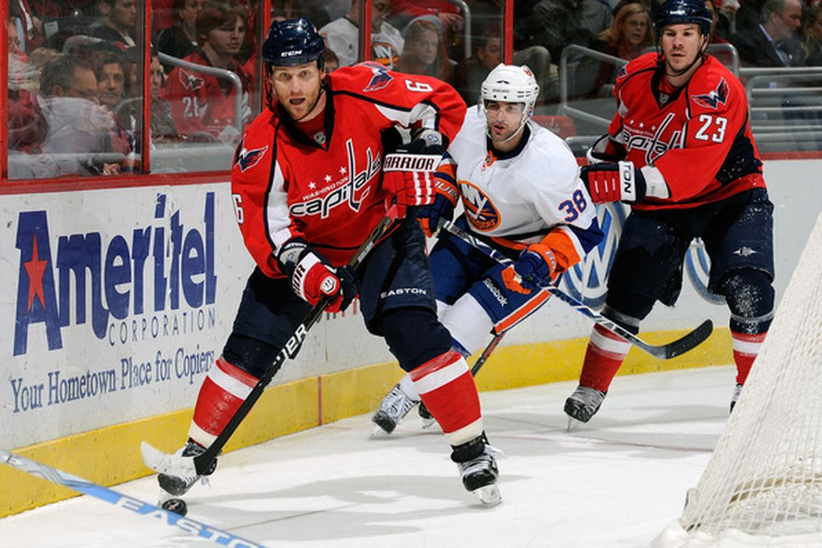 WASHINGTON, DC - MARCH 01:  Dennis Wideman #6 of the Washington Capitals brings the puck around the net against Jack Hillen #38 of the New York Islanders at the Verizon Center on March 1, 2011 in Washington, DC.  (Photo by Greg Fiume/Getty Images)