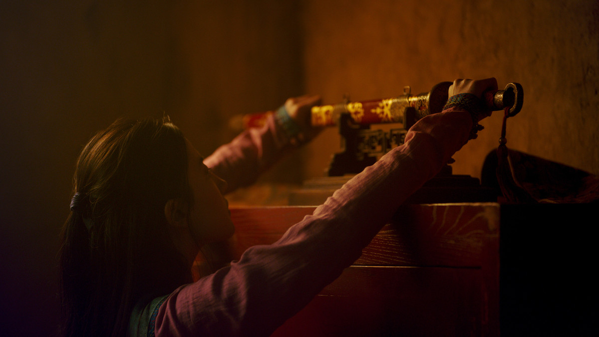 Mulan reaching for a sword in the live-action Mulan film.