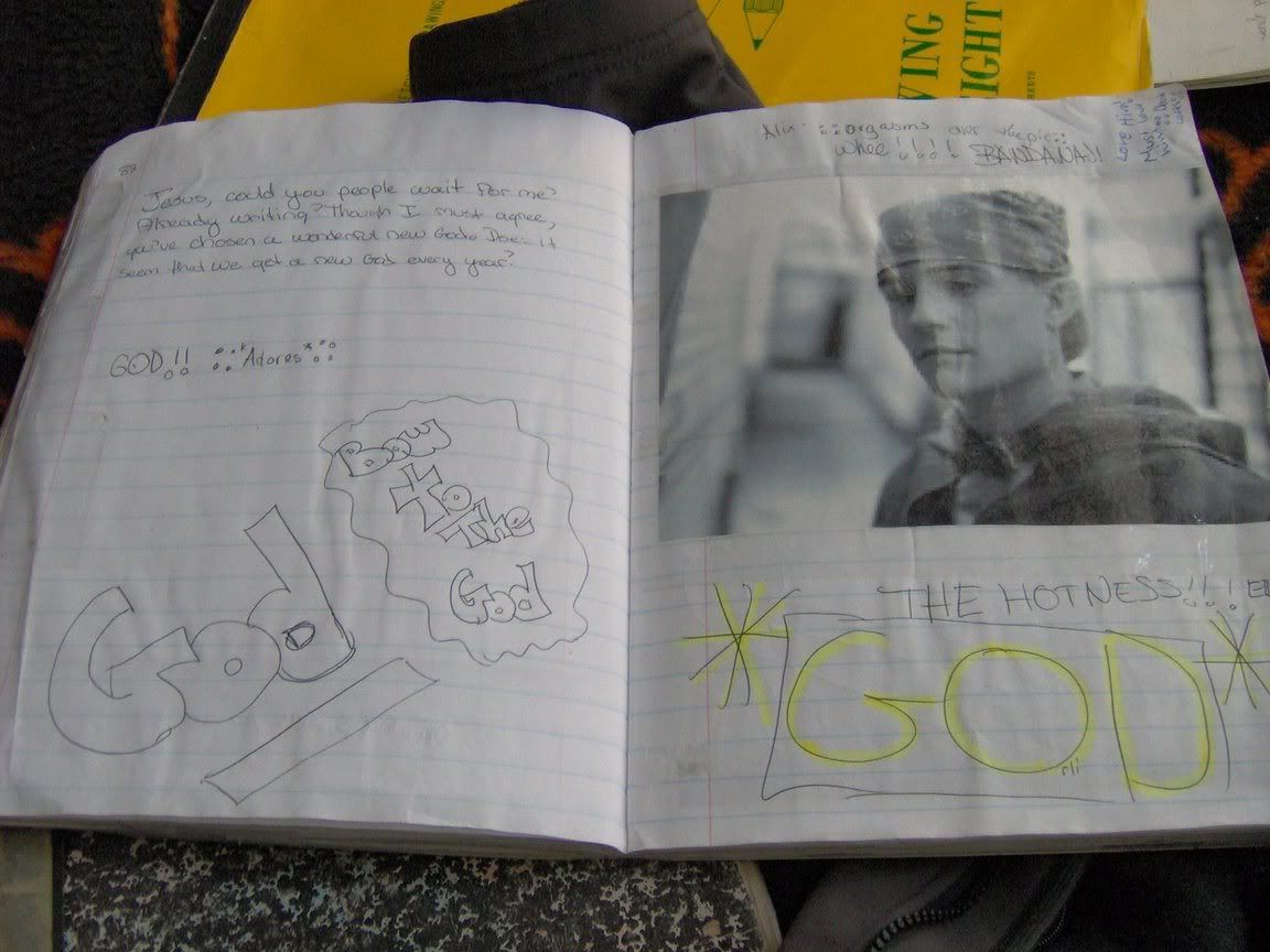 """A lined notebook, with a black and white picture of Orlando Bloom wearing a hooded sweatshirt and a bandanna. """"THE HOTNESS!!! *GOD*"""" is written below the photos in enormous letters and yellow highlighter."""