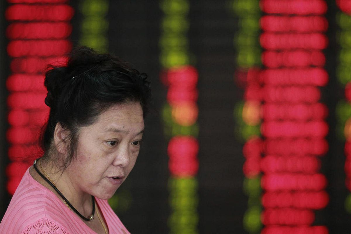 An investor looks at the stock price monitor at a private securities company in Shanghai, China, Tuesday Sept. 25, 2012. Asian stock markets were held in check Tuesday by a host of concerns about the global economy.