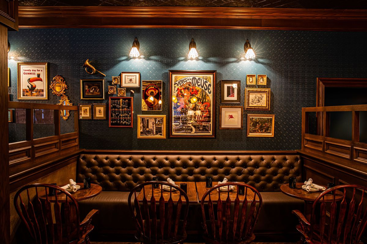The interior of a British-style pub, with warm, wood paneling, dark leather booths and Guinness posters and other art on a dark teal wall.