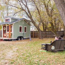 Meg and Dan Stephens relax on a bench outside their tiny house.