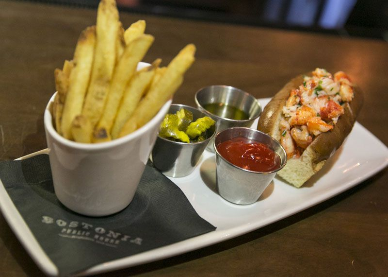 A lobster roll and fries served on a rectangular white plate, with pickles, ketchup, and vinegar