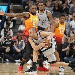 San Antonio Spurs' Manu Ginobili (20) tries to drive past Utah Jazz's Jae Crowder (99) as Spurs' LaMarcus Aldridge watches during the second half of an NBA basketball game Friday, March 23, 2018, in San Antonio. San Antonio won 124-120 in overtime. (AP Photo/Darren Abate)