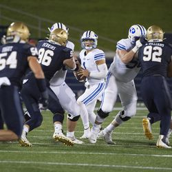 BYU quarterback Zach Wilson, center, looks to throw downfield as Navy defensive tackles Jackson Perkins (96) and Deondrae Williams (92) apply pressure during the first half of an NCAA college football game, Monday, Sept. 7, 2020, in Annapolis, Md.