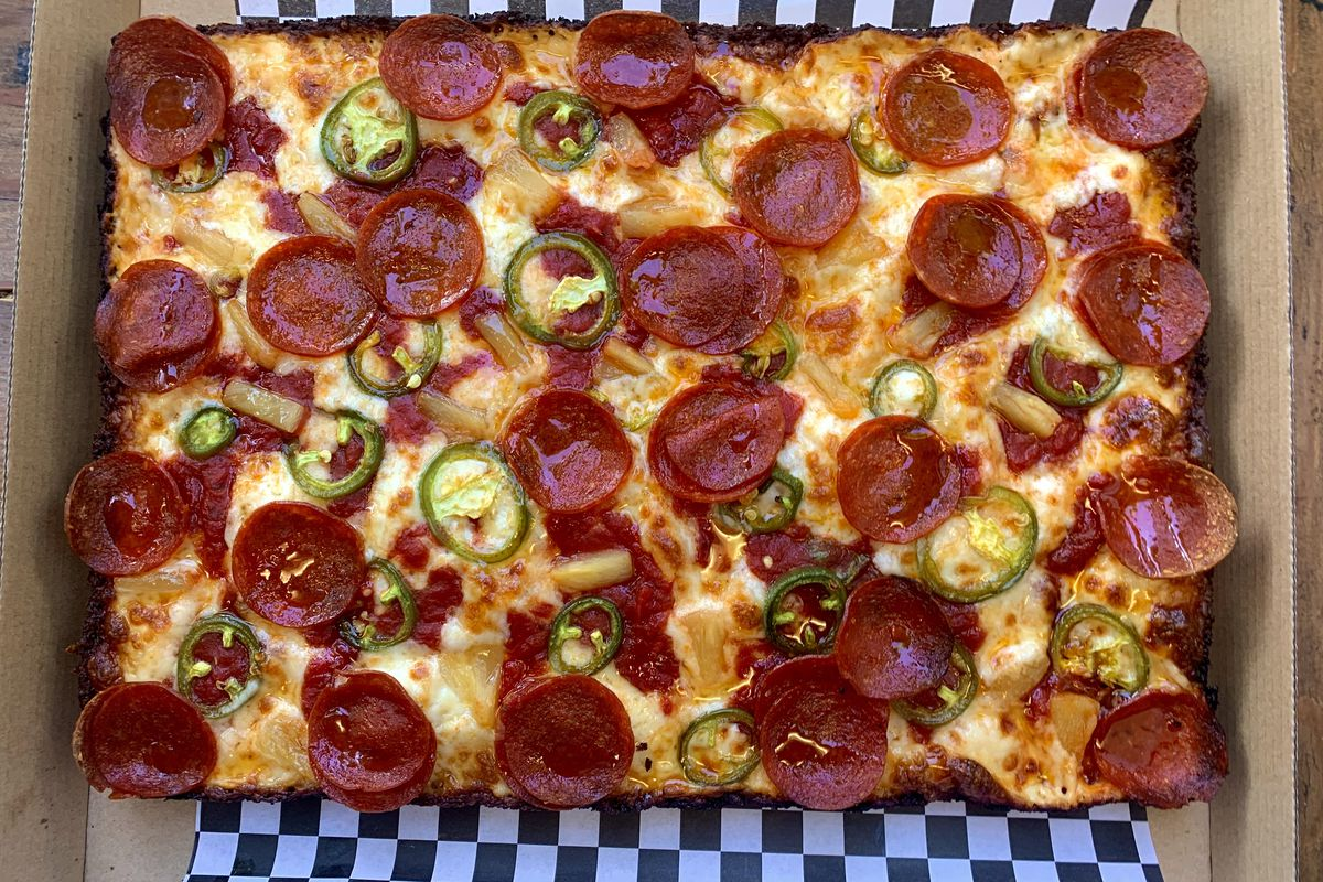 A square pizza topped with chunks of pineapple, pepperoni, jalapeno, and hot honey, sitting on a checkered piece of paper in a takeout box. This pizza, from the Precious Pizza Project pop-up in Portland, Oregon, will be available at the incoming Barley Pod cart.