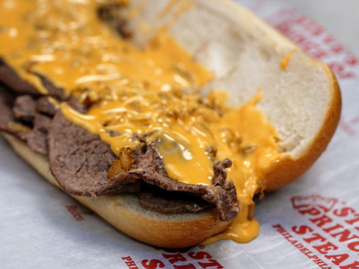 a cheesesteak with cheez whiz on white and red paper