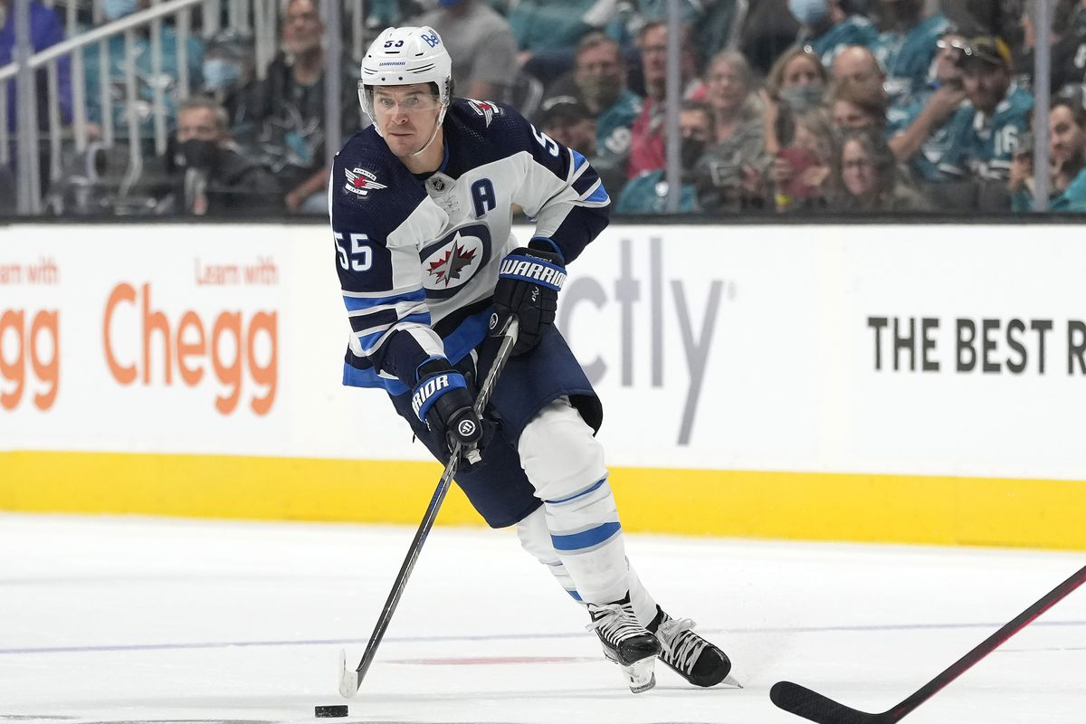 Mark Scheifele #55 of the Winnipeg Jets skates up ice with control of the puck against the San Jose Sharks during the third period at SAP Center on October 16, 2021 in San Jose, California.