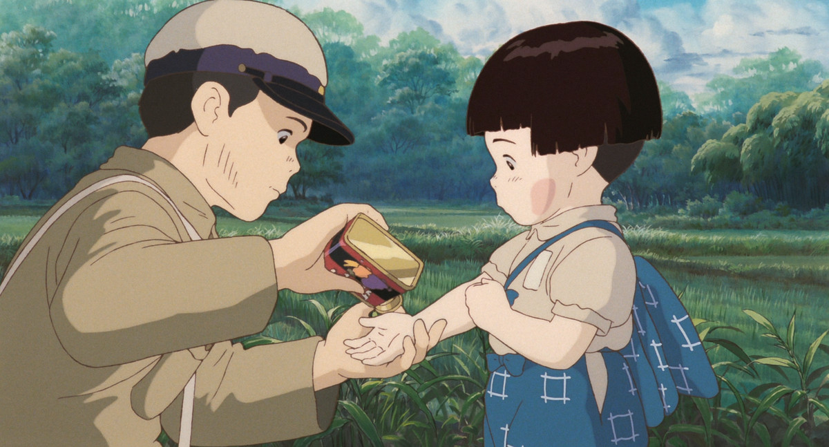 A young boy holds his sister's hand as he pours a piece of candy out of a tin for her in Grave of the Fireflies
