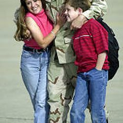 """Master Sgt. Raymond Weinmann greets his wife, Denise, and son Casey. """"I wouldn't trade this feeling for anything in the world,"""" he said. """"It's hard while you're there, but this makes it all worth it,"""" he said. It was his ninth rotation to the desert."""