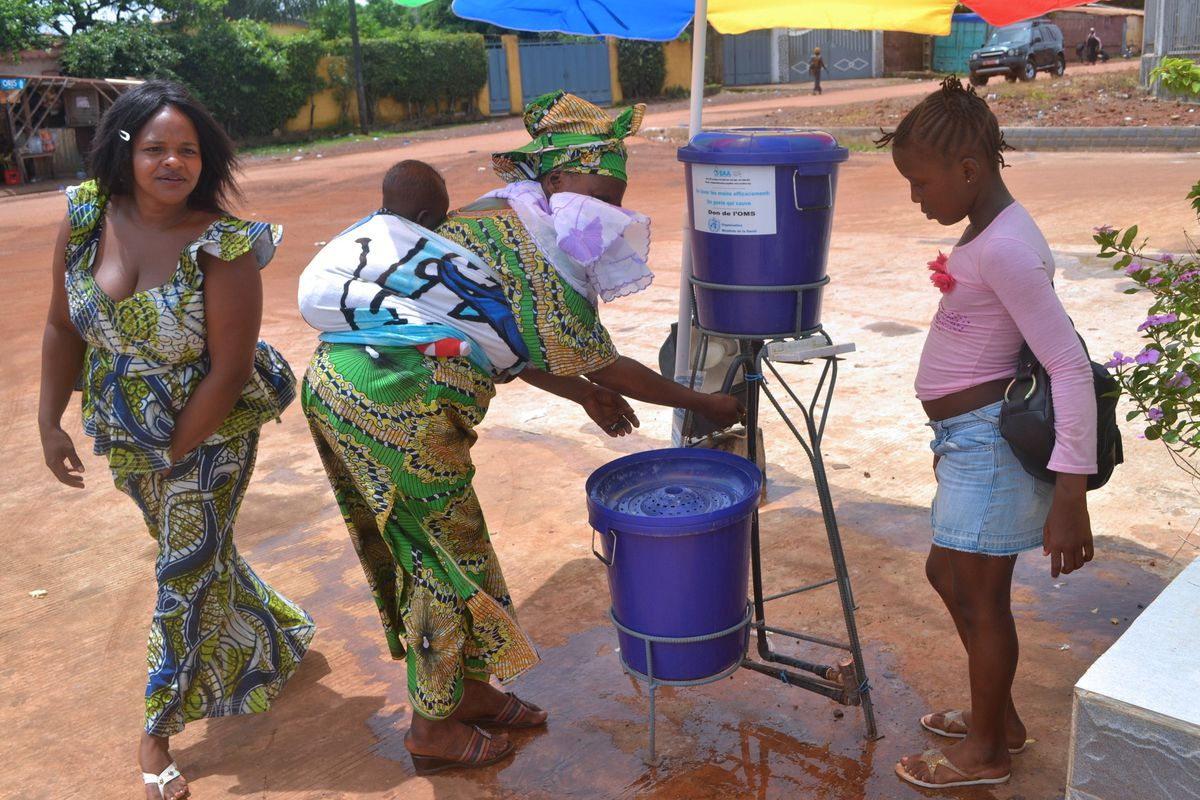 Guinean women washing their hands at the entrance of the Sino-Guinean hospital where Ebola patinets have been treated.