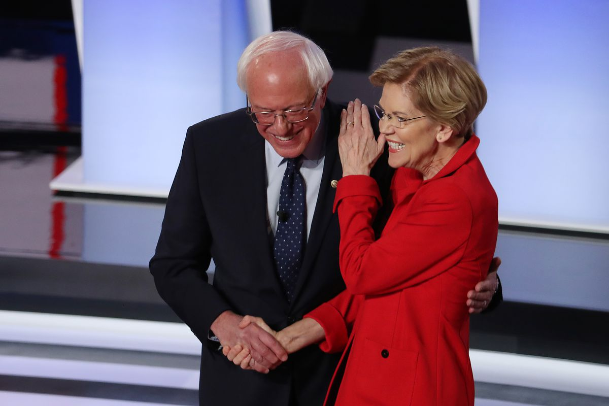 Senators Bernie Sanders and Elizabeth Warren shake hands and partially embrace as they take the Democratic debate stage on July 30, 2019.