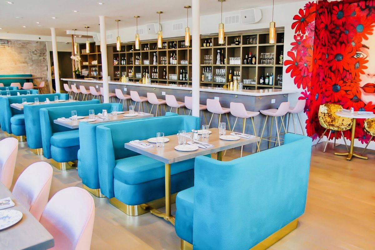 Bright blue booth seating stretches parallel to a bar with white stools and alcohol bottles lining the rear wall
