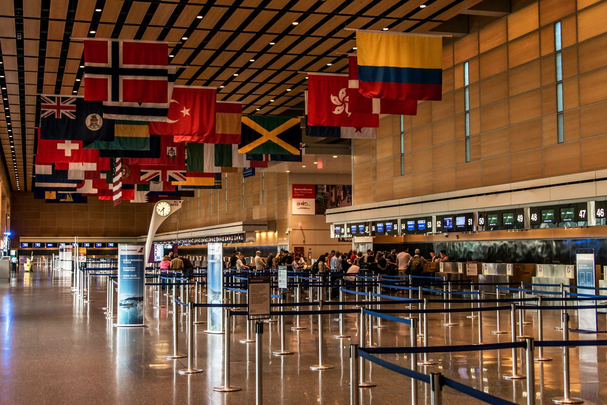 A cavernous airport terminal with flags hanging from the ceiling and people at ticket counters.