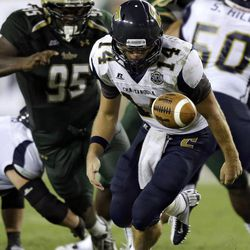 Chattanooga quarterback Jacob Huesman (14) chases after his own fumble before being sacked by South Florida defensive tackle Todd Chandler (95) during the fourth quarter of an NCAA college football game Saturday, Sept. 1, 2012, in Tampa, Fla.