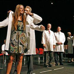Medical student Ashlie Berhisel receives her white coat Friday from Dr. David J. Bjorkman, the U. medical-school dean.