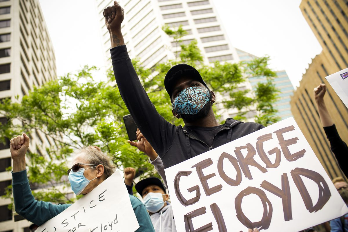 "A young black man flanked by a woman with grey hair raises his fist. His sign simply reads, ""George Floyd."""