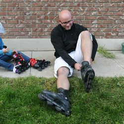 Kelly Logan, right, and his 8-year-old daughter Mykenzie put on their roller blades before playing outside Sept. 25.