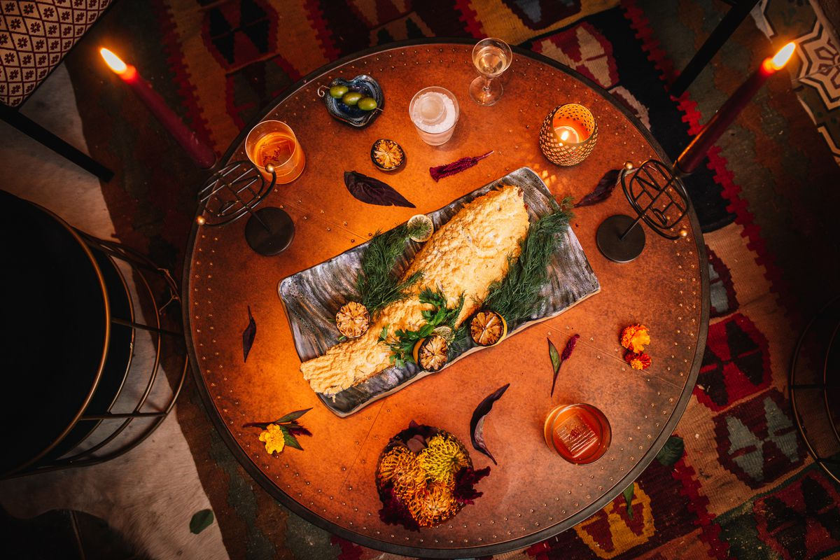 An aerial view of a table with candles and a whole branzino in the center