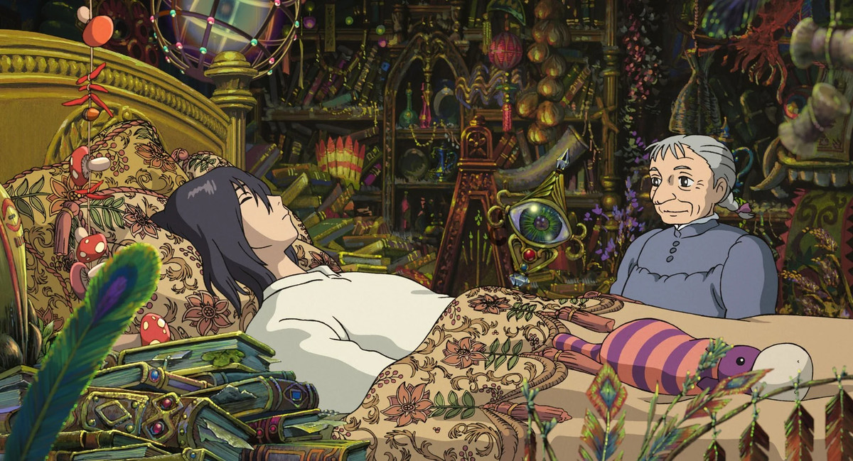 An old woman regards a young man sleeping in an elaborate bed in Howl's Moving Castle