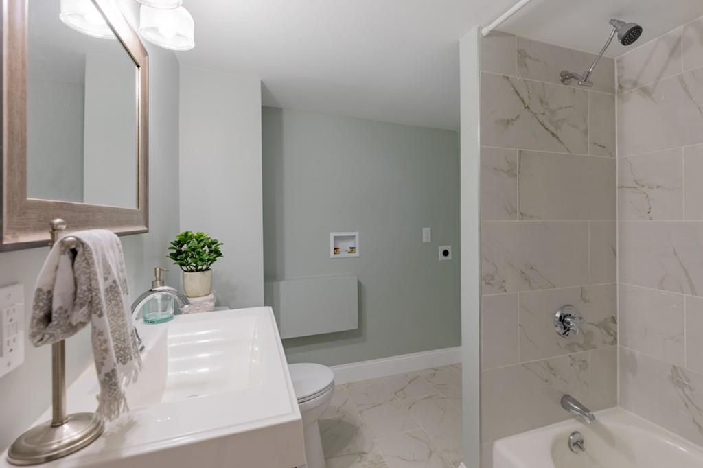 A narrow bathroom with no curtain on the shower.