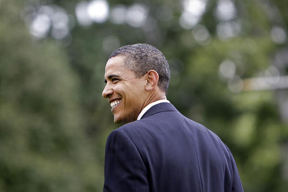 President Barack Obama smiles as he walks to a Marine helicopter at the White House to go on vacation.