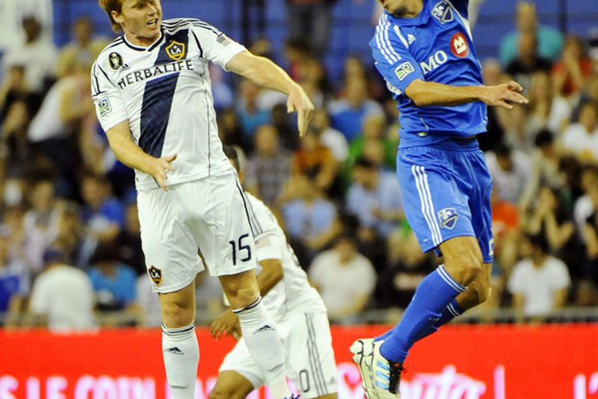 May 12, 2012; Montreal, QC, Canada; Los Angeles Galaxy midfielder Dan Keat (15) takes a header while Montreal Impact midfielder Davy Arnaud (22) defends during the first half  at the Olympic Stadium.  Mandatory Credit: Eric Bolte-US PRESSWIRE