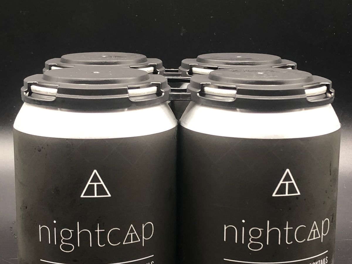 A four-pack of canned nightcap cocktails with a black and white label.