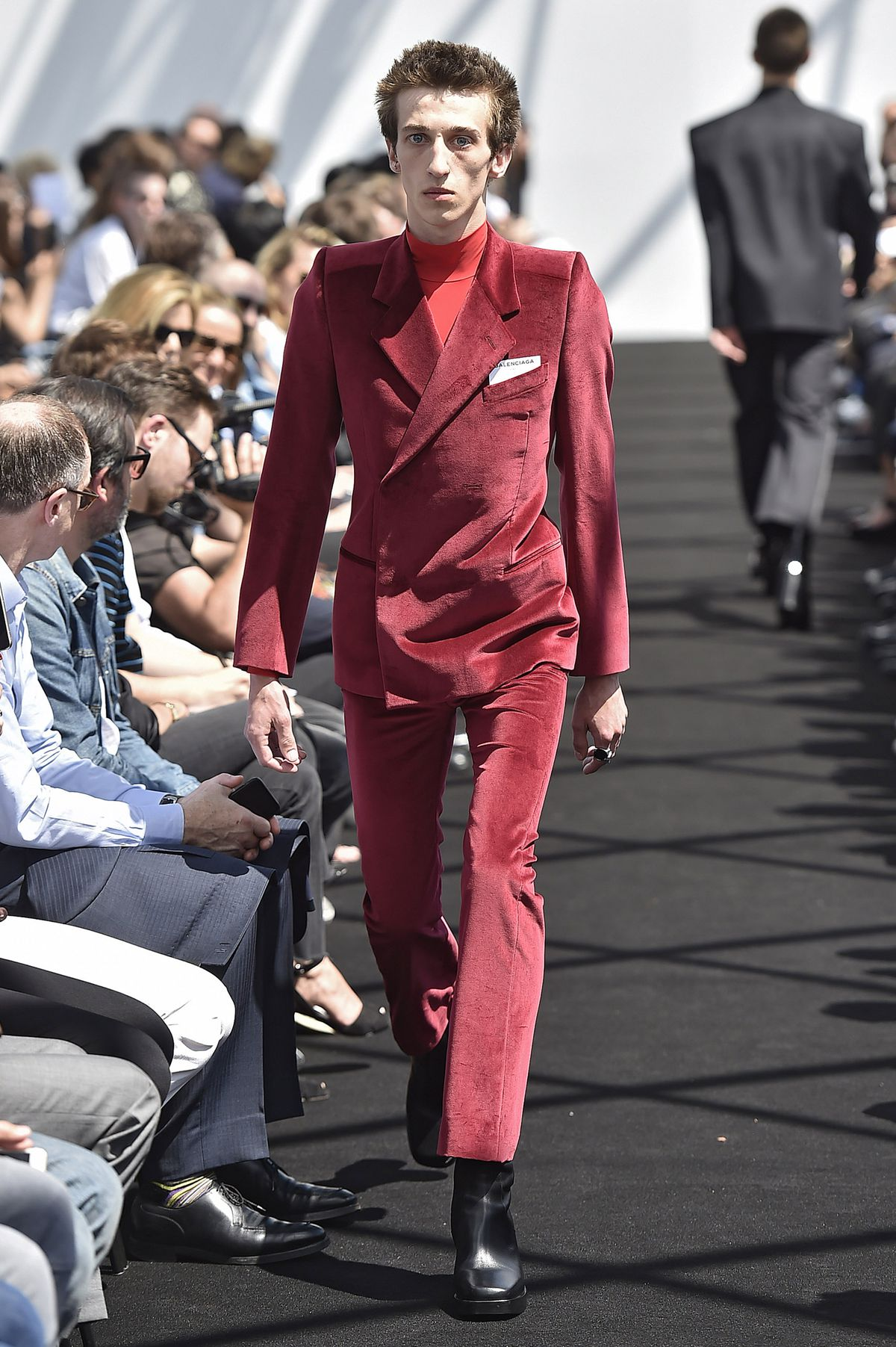 A model walks the runway wearing a pinched red velvet jacket and pants.