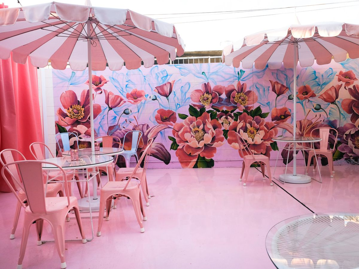 A floral mural with two tables with pink umbrellas in front of it.
