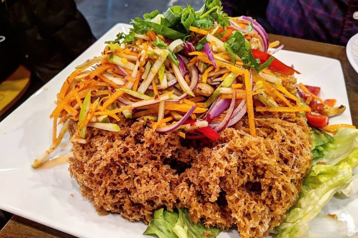 A cloud of crispy fried catfish topped with a salad of thinly sliced green apple, carrot, and red onion