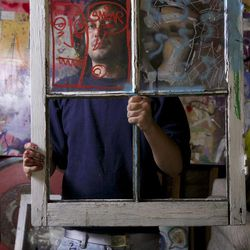 """In this photo taken on Monday March 28, 2011, artist Cristian Gheorghiu holds one of his works at his East Hollywood garage studio in Los Angeles. Gheorghiu, known by his nickname of """"Smear,"""" faces an injunction that could bar him from profiting from art bearing his telltale graffiti """"tag."""" But Gheorghiu's lawyer says the city attorney's lawsuit is a thinly-veiled attempt around the First Amendment right to free expression."""