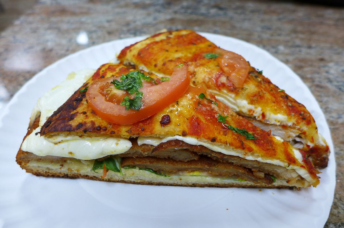 A wedge shaped sandwich with a split focaccia that looks like two slices of pizza on top and bottom.