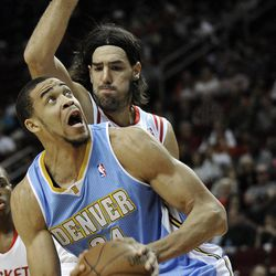 Denver Nuggets' JaVale McGee (34) looks to the basket as Houston Rockets' Luis Scola defends during the first half of an NBA basketball game Monday, April 16, 2012, in Houston.