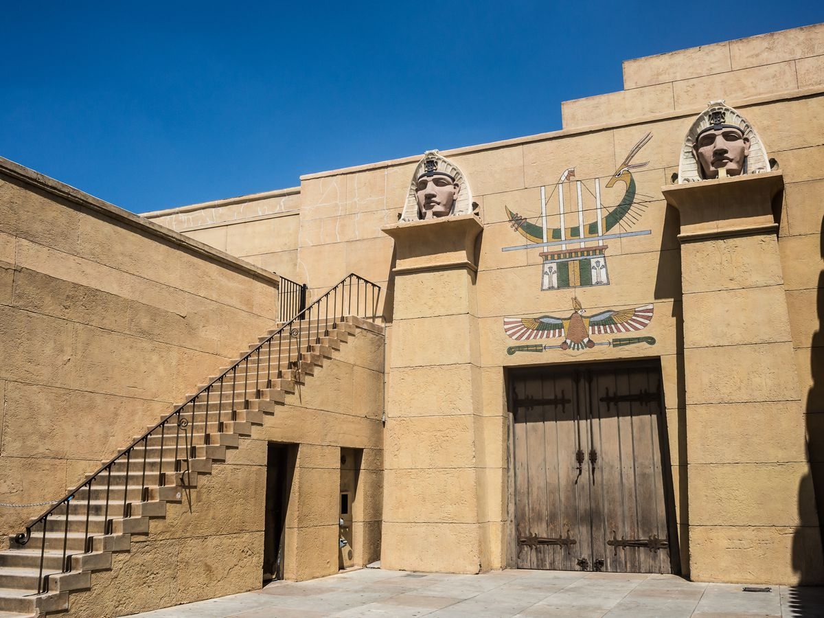 The exterior of a theatre. The facade is tan stone. There are Egyptian pharaoh heads above columns on both sides of the door.