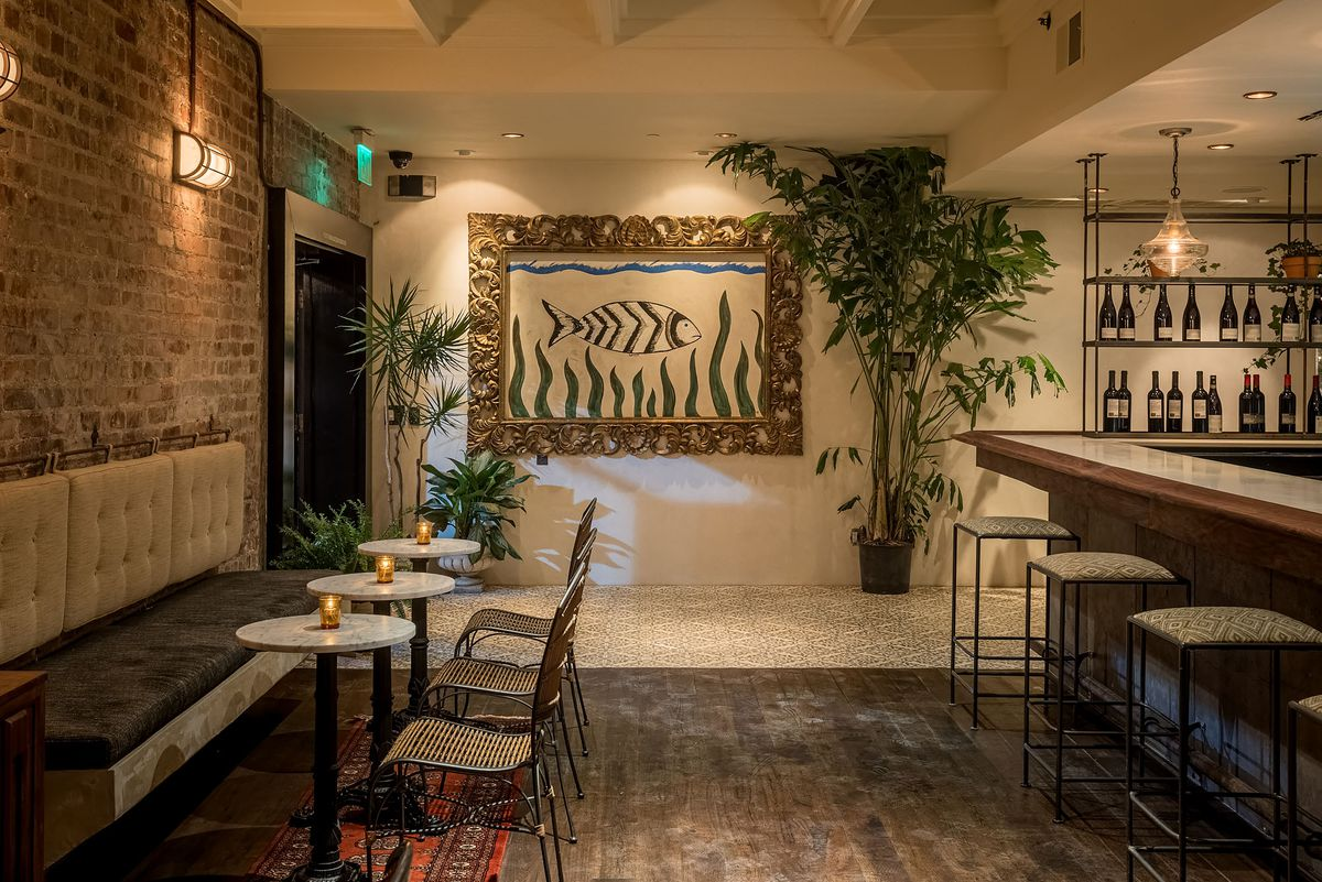 A fish tile art and lots of brick surround seating and plants in the dark bar.