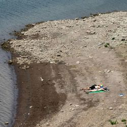People sunbathe on the shores of East Canyon Reservoir on Tuesday, June 25, 2013. Utah is facing drought conditions this summer.