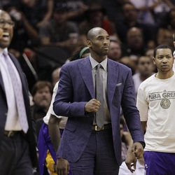 Los Angeles Lakers' Kobe Bryant, center, wears street clothes during the first quarter of an NBA basketball game against the San Antonio Spurs, Wednesday, April 11, 2012, in San Antonio. Bryant is out with a left shin injury.