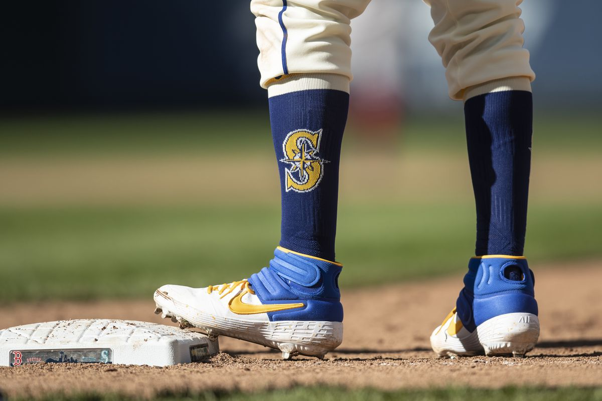 Tim Beckham of the Seattle Mariners wears Nike spikes and socks sporting the Mariners logo whiles standing on first base during a game against the Boston Red Sox at T-Mobile Park on March 31, 2019 in Seattle, Washington.